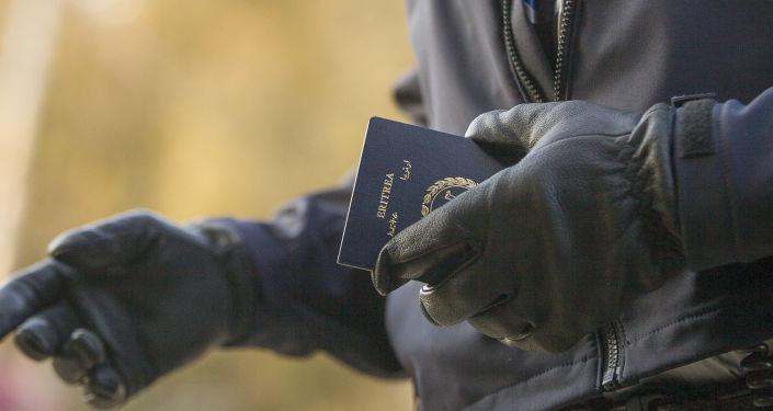 Officier de la police aux frontières tient le passeport d'une femme érythréenne après son passage illégal de la frontière américano-canadienne. Québec
