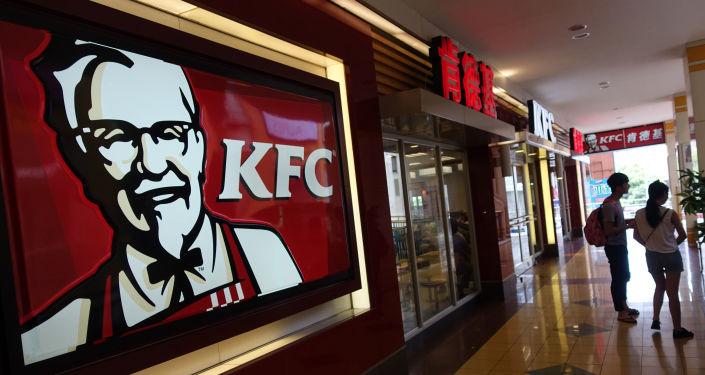 Deux personnes passent devant un restaurant KFC à Shanghai