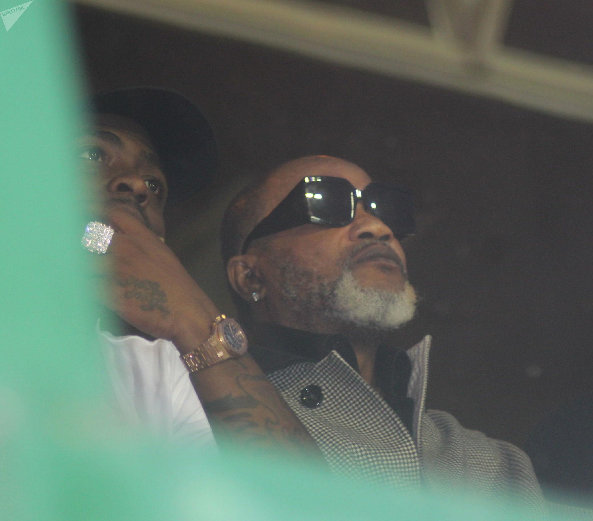 Les stars de la musique congolaise Kofi Olomidé (en lunettes de soleil), et nigériane Davido, assises côte à côte peu avant la présentation de la dépouille de DJ Arafat.