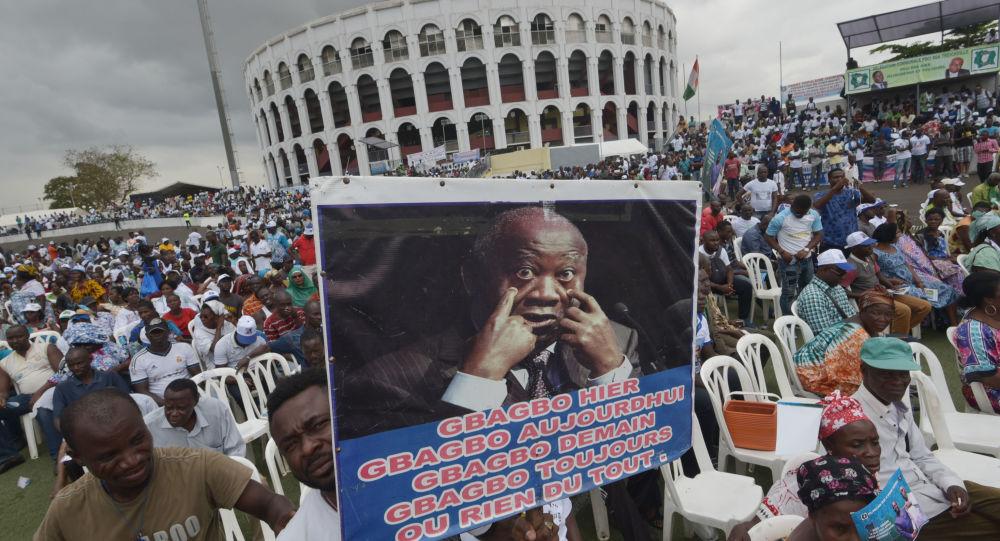 Un homme tient une pancarte montrant une photo de Laurent Gbagbo