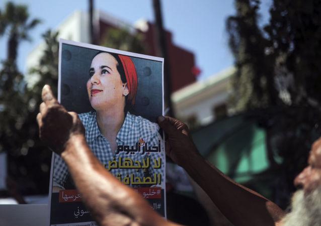 Un homme brandissant un portrait de Hajar Raissouni à Rabat