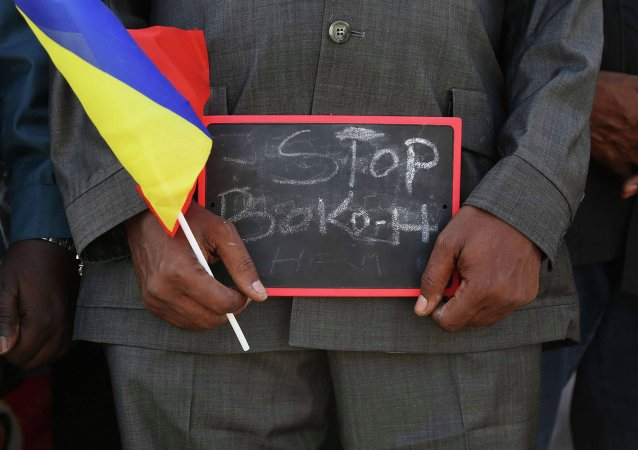 A man holds a sign that reads Stop Boko Haram at a rally to support Chadian troops heading to Cameroon to fight Boko Haram, in Ndjamena January 17, 2015.