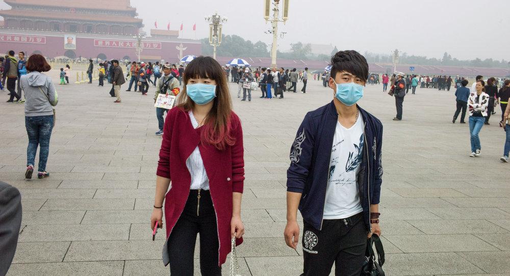 Un couple aux masques respiratoires sur la Place Tiananmen à Pékin
