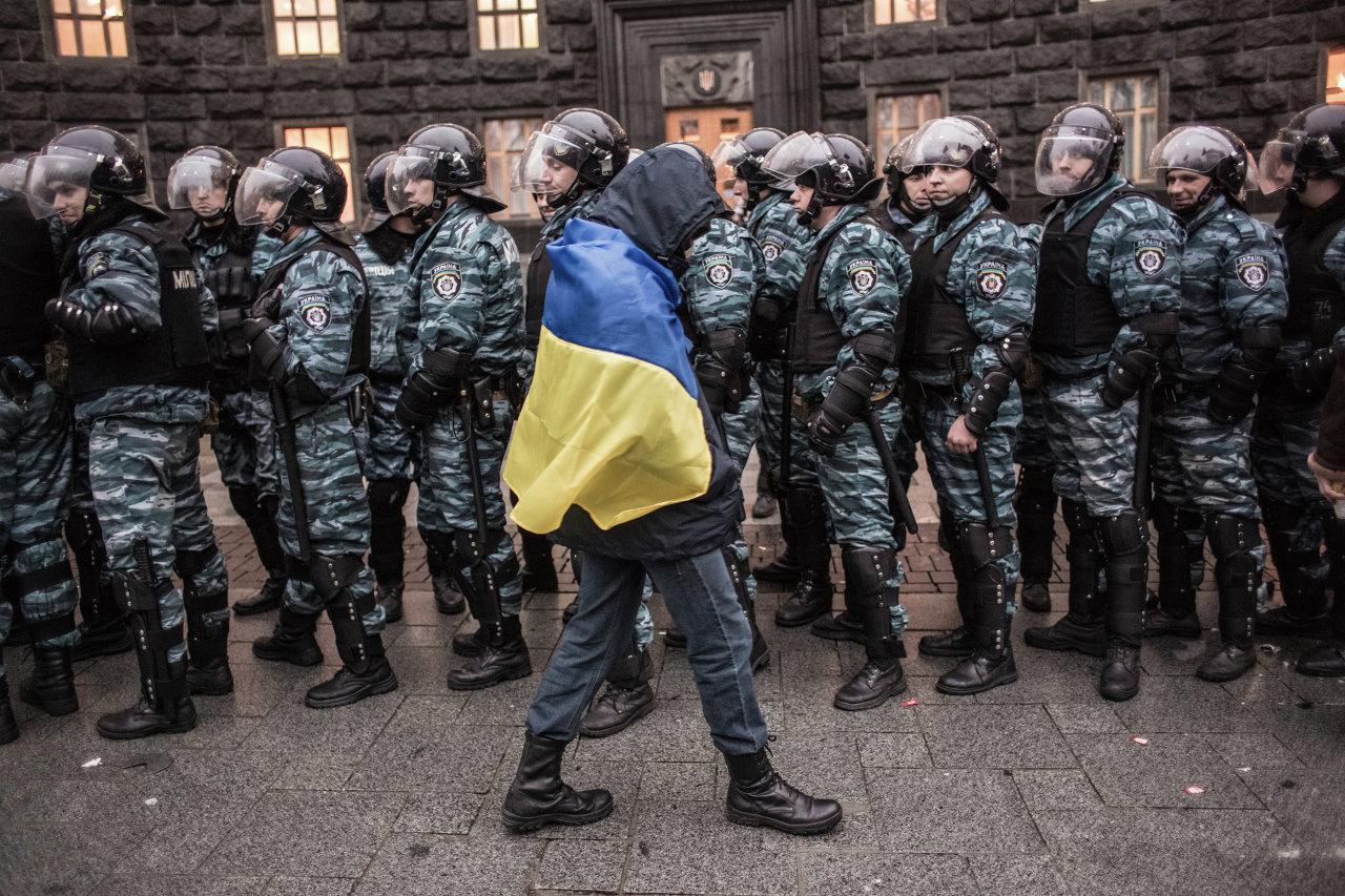 Un partisan de l'intégration européenne de l'Ukraine et des policiers devant le siège du gouvernement ukrainien à Kiev