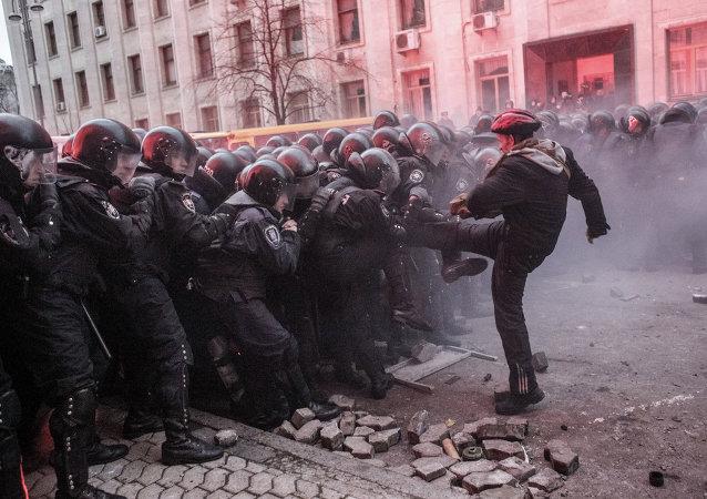Un partisan de l'intégration européenne de l'Ukraine face à la police lors de troubles en face du bâtiment de l'administration présidentielle à Kiev