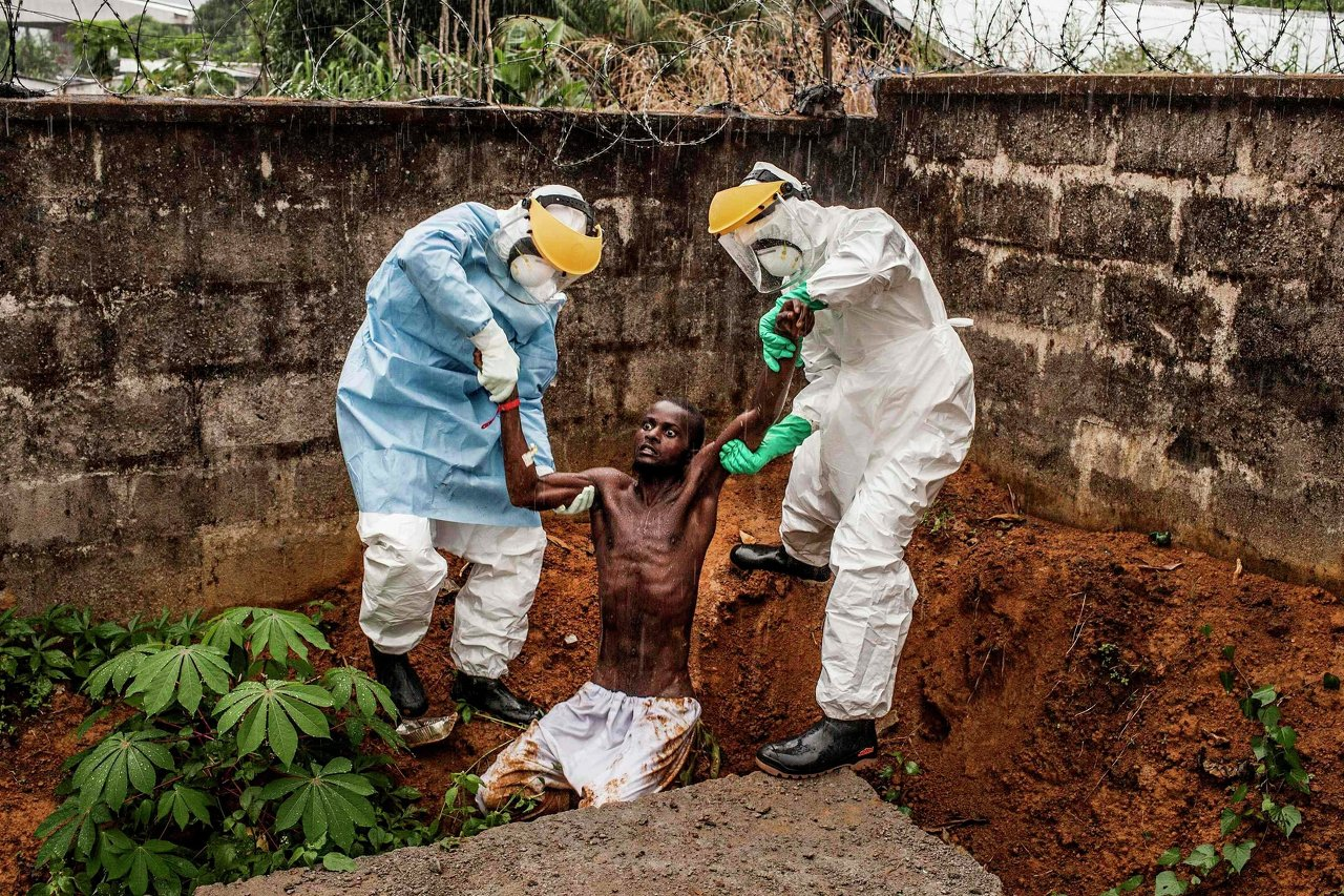 Des membres d'une équipe médicale du centre de traitement pour les malades d'Ebola prennent en charge un patient en phase de délire en Sierra Leone