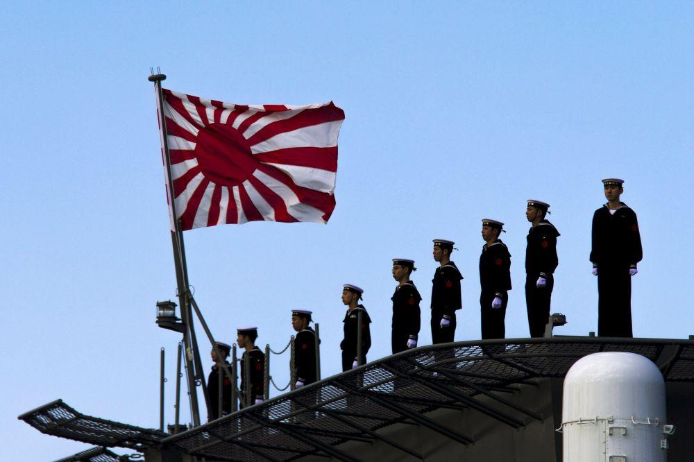 Des marins alignés sur le pont de l'Izumo lors de la cérémonie de mise en service du porte-hélicoptères dans le port de Yokohama