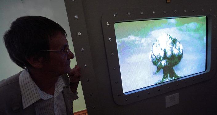 Un homme contemplant l'image d'une explosion nucléaire