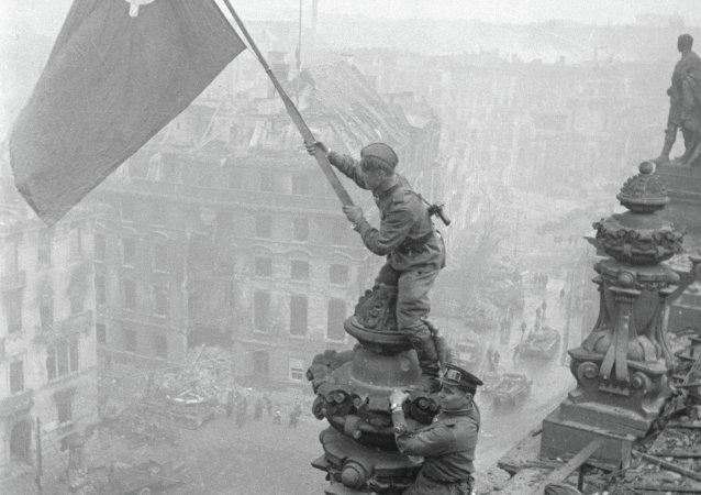 Un soldat de l'Armée rouge hisse le drapeau soviétique sur le Reichstag