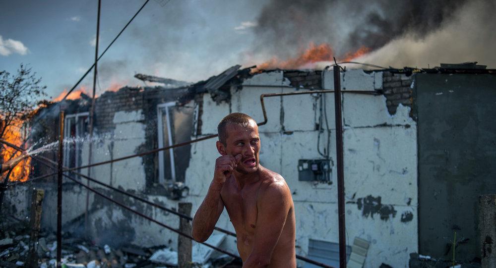 Un habitant du village de Louganskaïa essaie d'éteindre un incendie provoqué par un raid aérien des forces gouvernementales ukrainiennes