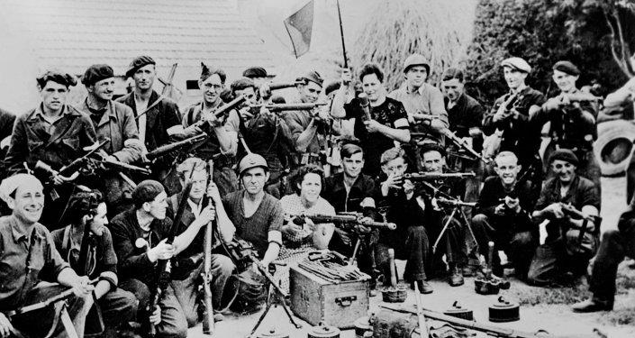 Un groupe de maquisards pose pour une photo avec armes et drapeau dans la cours d'une ferme en France, en un lieu indéterminé, durant l'été 1944, pendant la seconde Guerre mondiale.
