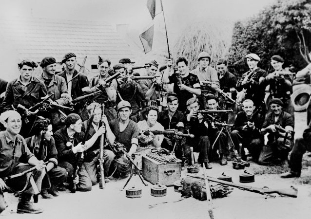 Un groupe de maquisards pose pour une photo avec armes et drapeau dans la cour d'une ferme en France, en un lieu indéterminé