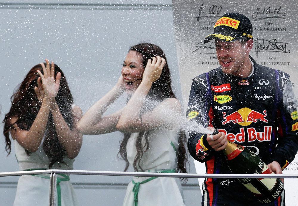 Grid-girls aspergées de champagne par le pilote allemand Sebastian Vettel au Grand Prix de Malaisie en 2013