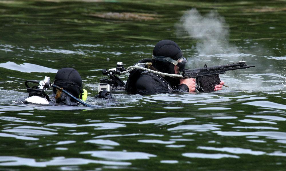 Un nageur de combat en train de tirer avec un fusil d'assaut sous-marin (APS