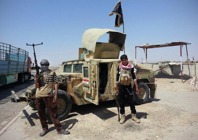 Des combattants de l'EI devant un tout-terrain militaire Humvee capturé à Mossoul