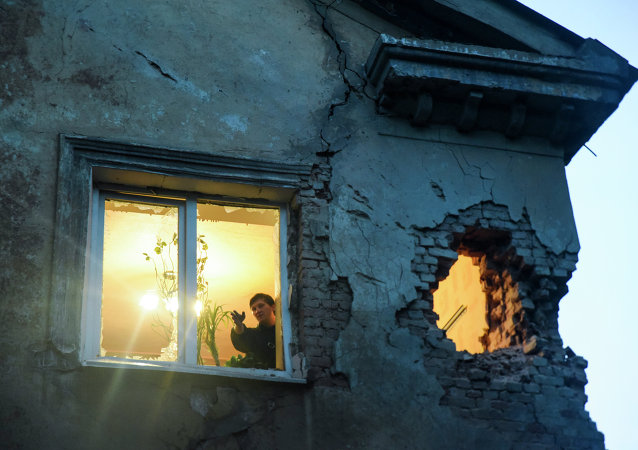 People observe damage in their flat after shelling between Russia-backed separatists and Ukrainian government troops in Donetsk, Eastern Ukraine Monday, June 1, 2015