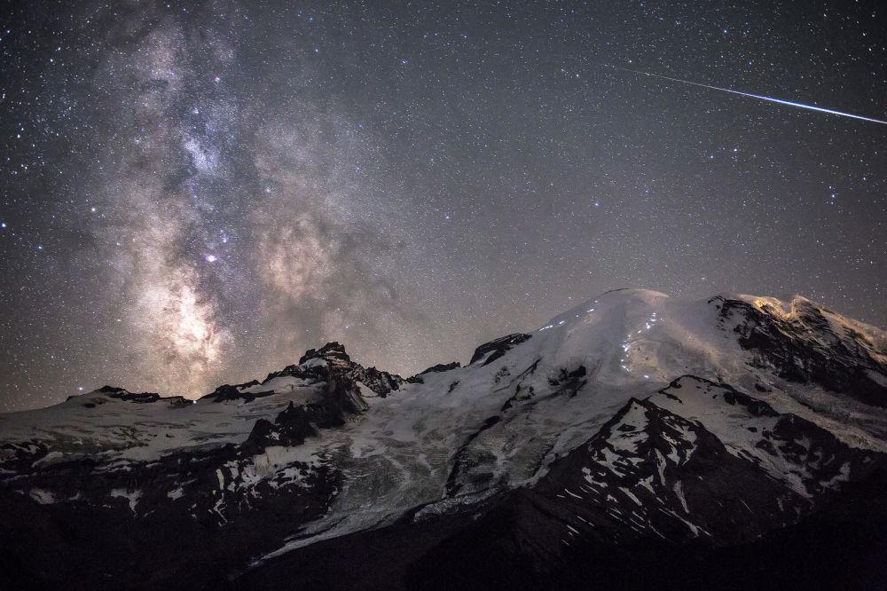 Une météorite traverse la Voie lactée. La photo est prise sur fond des sommets du parc national Mount Rainer dans l'Etat de Washington, USA