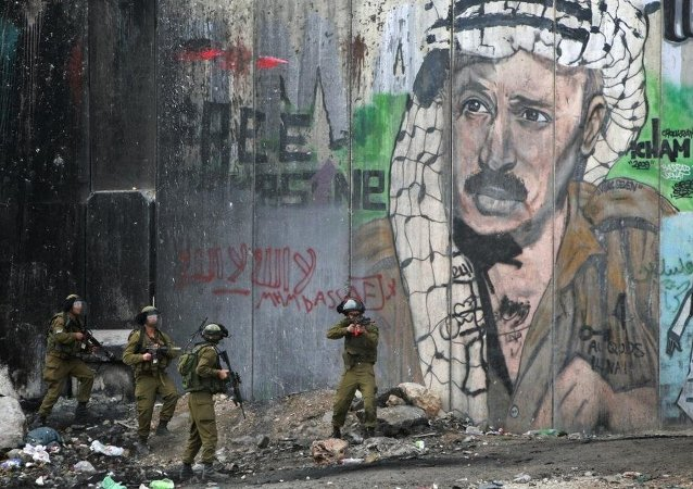 Des soldats israéliens face à un portrait de Yasser Arafat