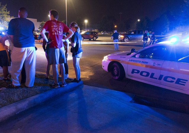 Bystanders watch over the scene at a movie theatre where a man opened fire on film goers in Lafayette, Louisiana July 23, 2015