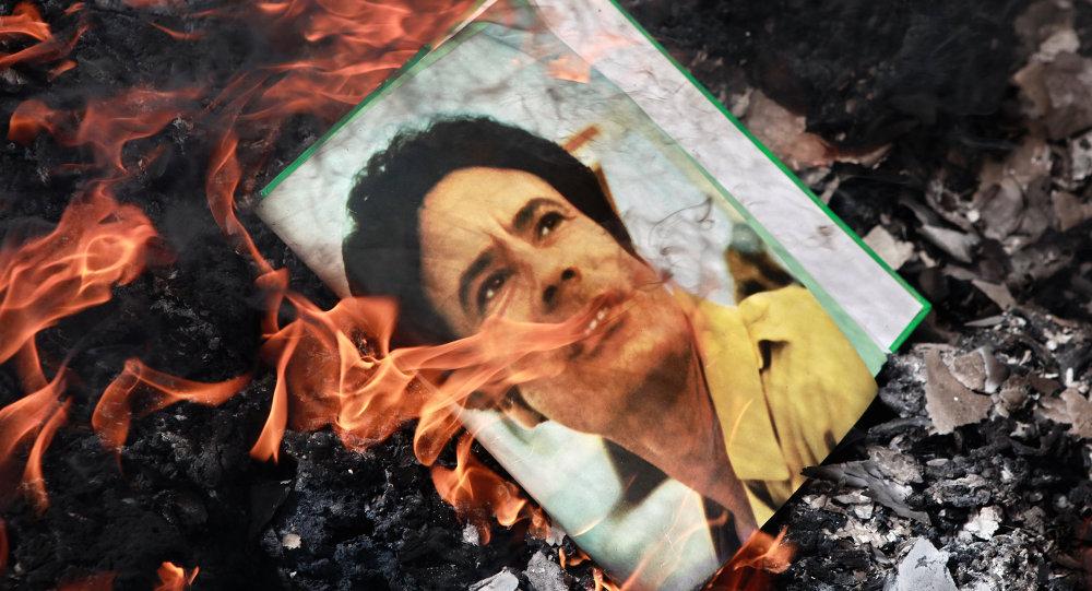 Un portrait de Mouammar Kadhafi brûlé par des manifestants