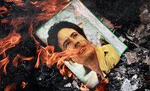 Un portrait de Mouammar Kadhafi brûlé par des manifestants.