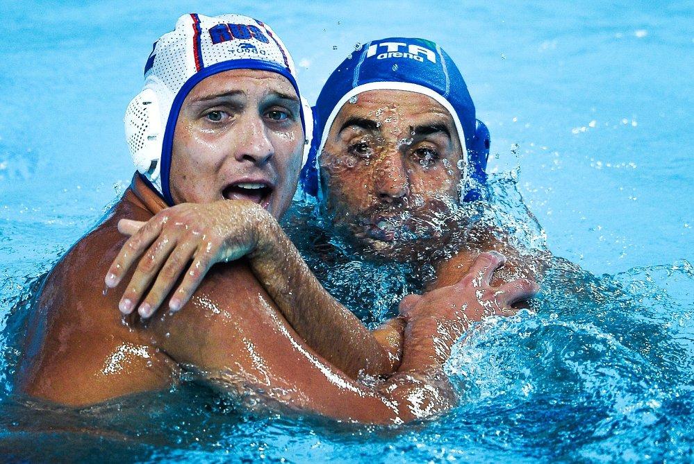 A gauche Alexey Bugaychuk (Russie), face à Alex Giorgetti (Italie) pendant le match du premier tour préliminaire de water-polo hommes