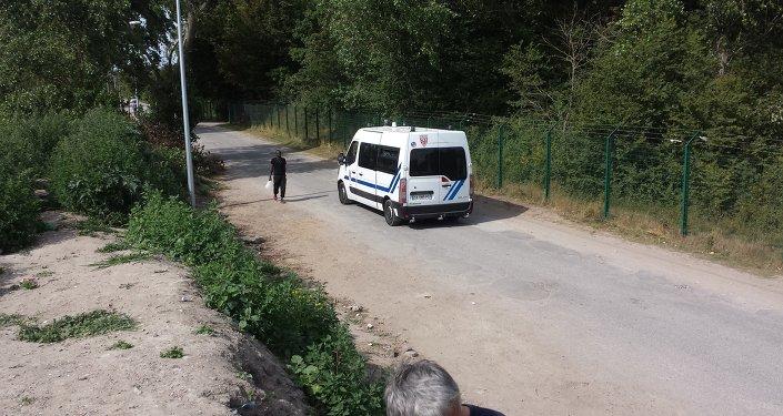 Voiture de police devant un camp de migrants