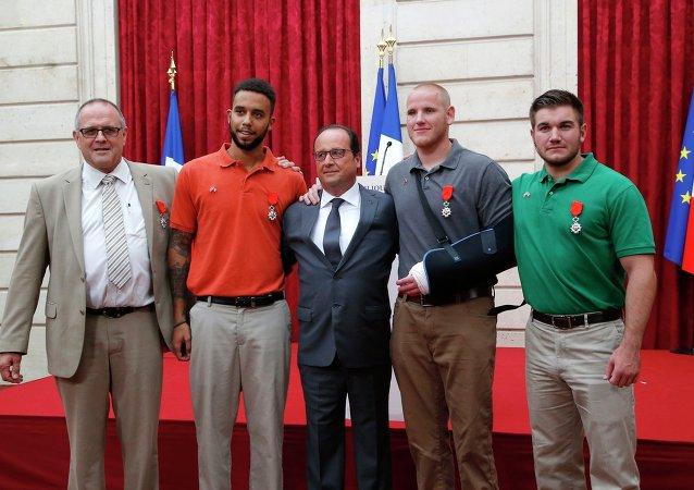 François Hollande pose avec les trois jeunes Américains héros du Thalys