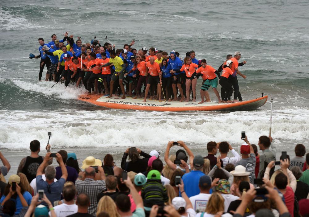66 surfeurs serrés sur une planche ont battu un record validé par le Livre Guinness