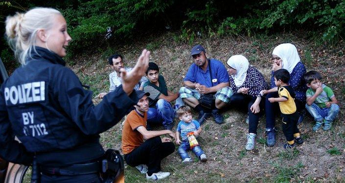 Une policière allemande se tient à côté de deux familles de réfugiés syriens près de Passau