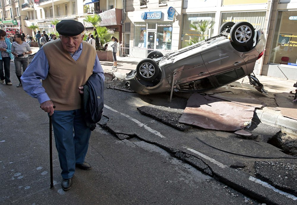 A man walks past an overturned car in the street that was damaged in flooding caused by torrential rain in Cannes, France, October 4, 2015