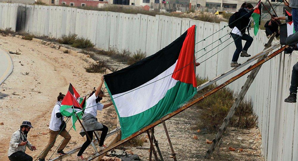 Les activistes étrangers et les manifestants palestiniens utilisent une rampe en métal pour traverser une section de la barrière israélienne controversée près du poste de contrôle Kalandia. Archive photo