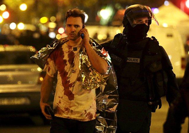 Un policier français accompagne un homme blessé dans l'attaque contre le Bataclan