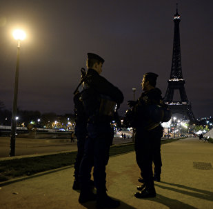 Police officers stand guard near the Eiffel Tower which has its lights turned off on November 14, 2015 following the deadly attacks in Paris.