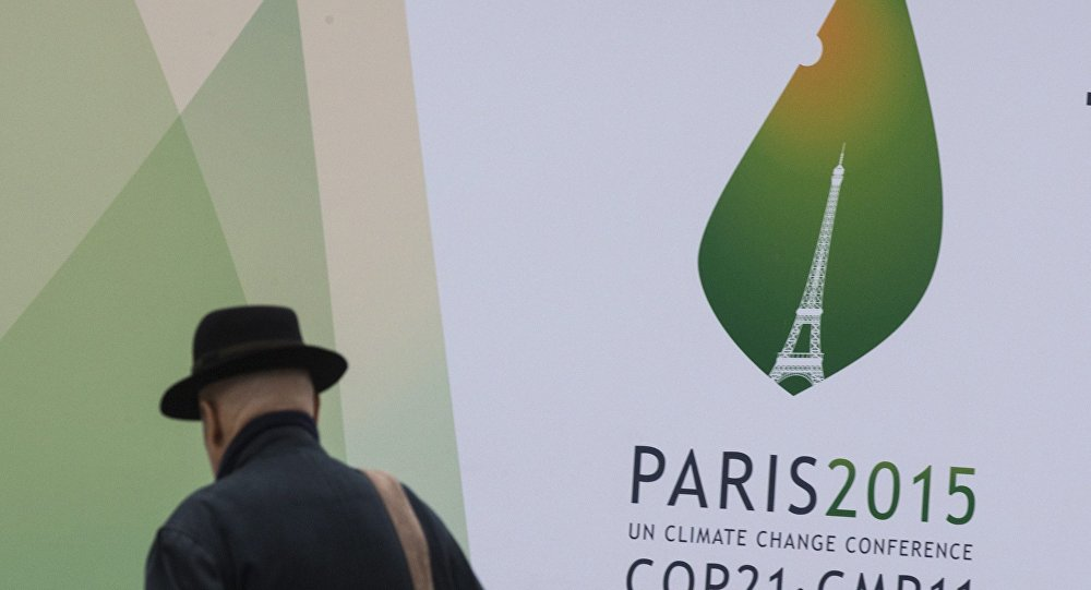 A passerby walks in front of posters for the forthcoming COP 21 World Climate Summit in Paris, France