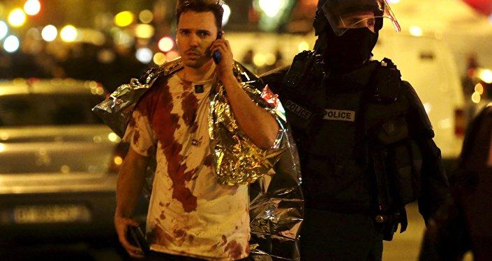 Un policier français assiste une victime près de la salle de concert du Bataclan à Paris, en novembre 2015
