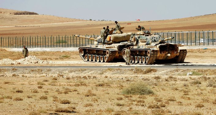 Turkish soldiers stand on top of tanks next to the Syrian-Trukish border fence