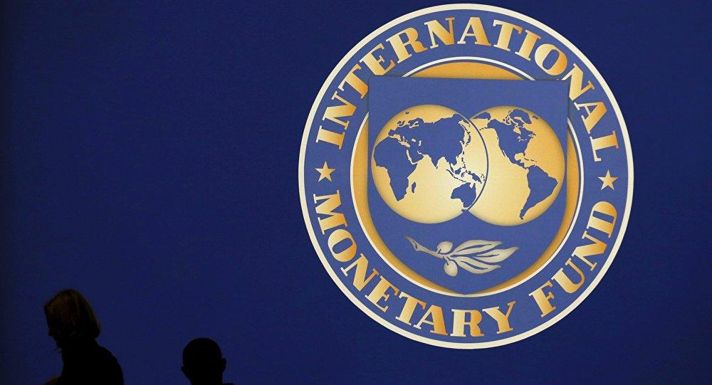 Les silhouttes des visiteurs sur le logo du Fonds monétaire international sur le site principal de la réunion annuelle du FMI et de la Banque mondiale à Tokyo Octobre 10, de 2012.