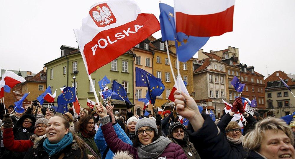 Les gens tiennent les drapeaux européens et polonais lors d'une manifestation à Varsovie, Pologne, le 9 janvier 2016