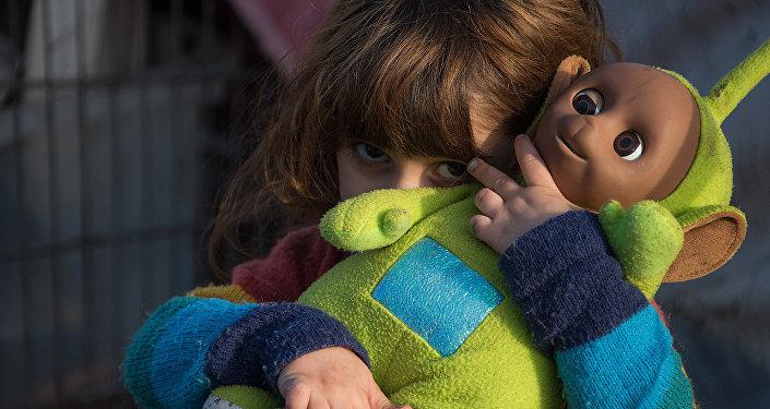 L'enfant de migrants kurdes devant une tente au camp de migrants Grande Synthe