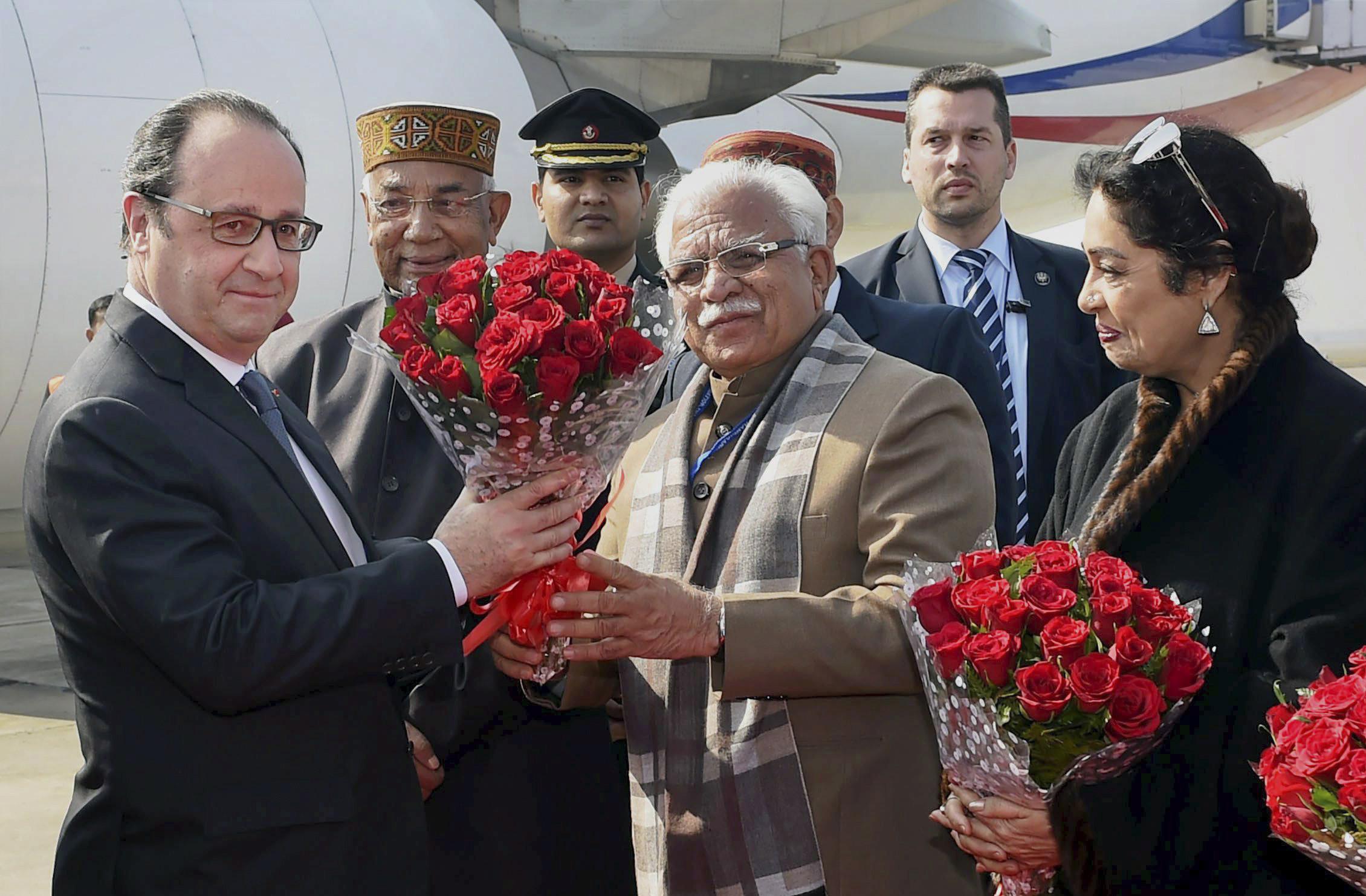 Le président français François Hollande, à gauche, reçoit des fleurs de Manohar Lal Khattar, le chef ministre de l'État d'Haryana, deuxième à droite, tandis que le gouverneur de l'État d'Haryana Kaptan Singh Solanki, deuxième à gauche, et député indienne Kirron Kher, à droite, se jointent en accueillant le président français à la base aérienne indienne de Chandigarh, en Inde, le dimanche 24 janvier 2016.