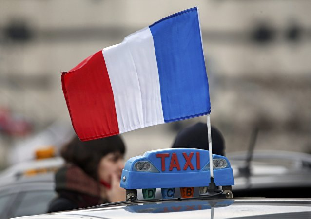 A French flag is seen on a striking taxi as drivers block traffic during a demonstration at Porte Maillot during a national protest about competition from private car ride firms like Uber, in Paris, France, January 26, 2016