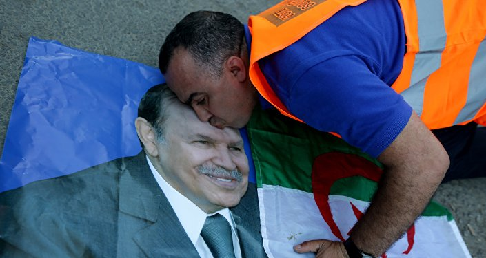A supporter of Algerian President Abdelaziz Bouteflika kisses his picture as he celebrates in Algiers on April 18, 2014 after Bouteflika won a fourth term with 81,53% of the votes.