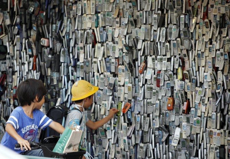 Sur la photo : les enfants regardent un mur avec des téléphones mobiles usagés sur un marché chinois