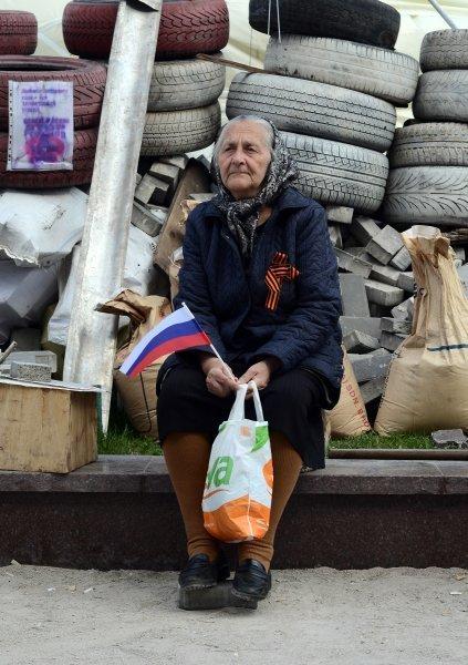 Photo : une partisane de la fédéralisation de l'Ukraine portant un ruban de Saint-Georges sur la place devant le bâtiment de l'administration de la région de Donetsk.