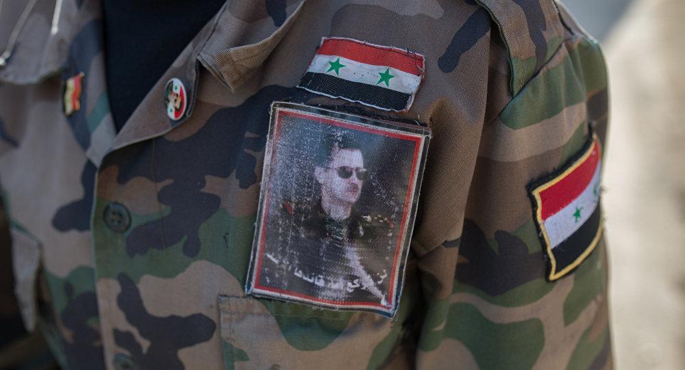 Un volontaie de l'armée syrienne porte un uniforme à l'effigie du président Assad