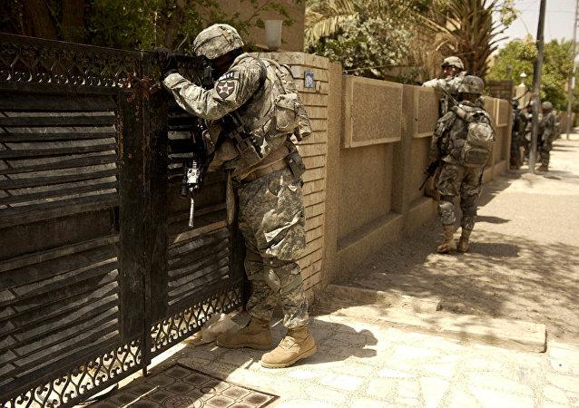Les soldats américains regardent dans la cour d'une maison. Irak