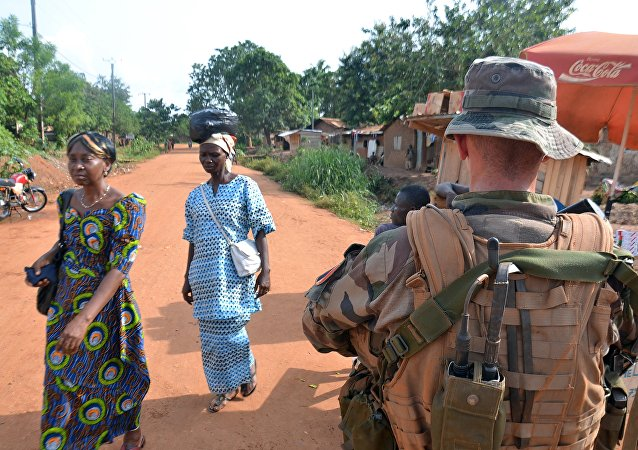 Women walk past a French soldier, part of Operation Sangaris, on patrol in the 6th district of the capital Bangui, on May 20, 2015.
