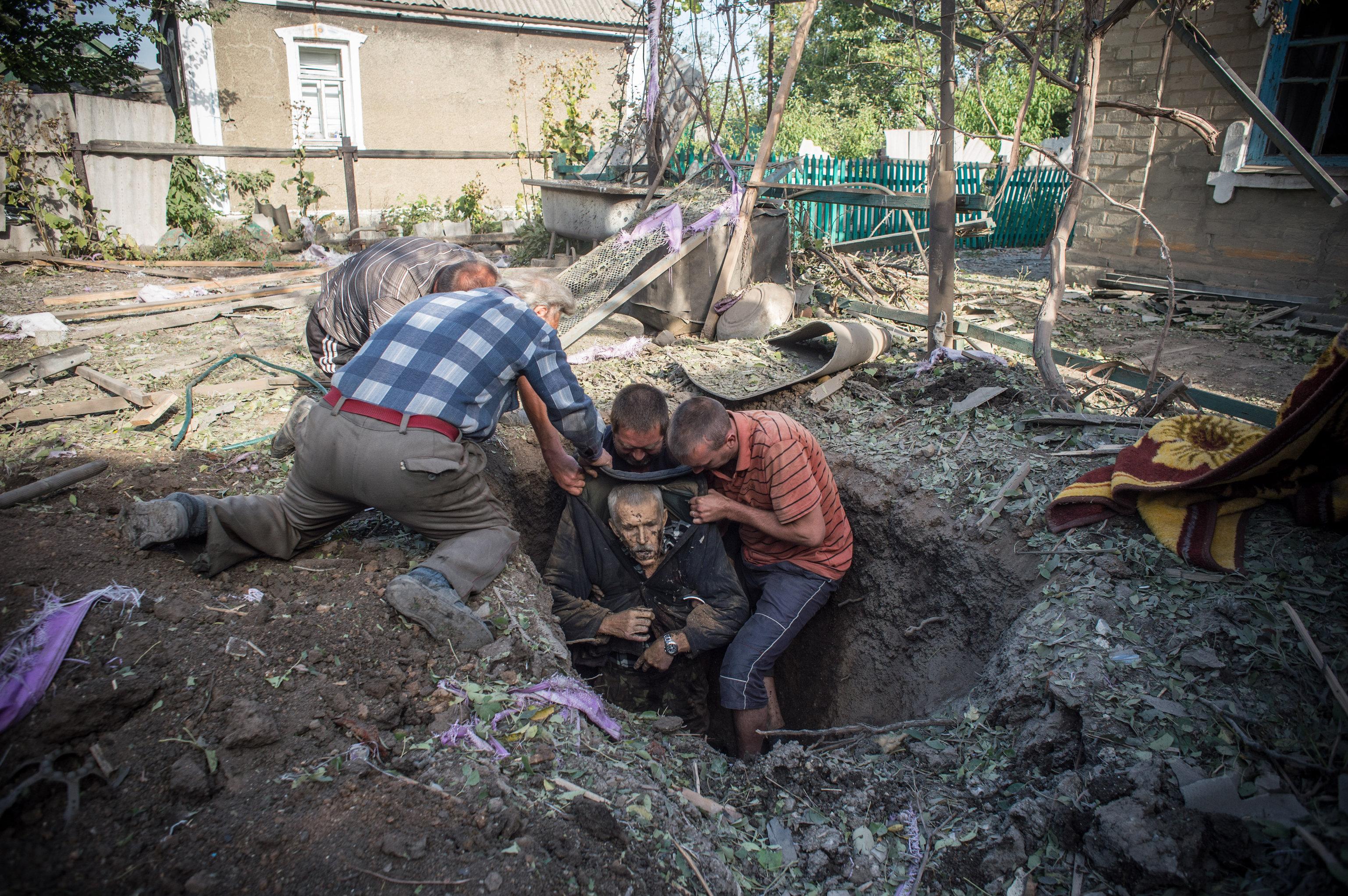 Les habitants locaux retirent le corps d'un homme tué lors des tirs d'artillerie dans le village d'Alexandrovka, dans la région de Donetsk