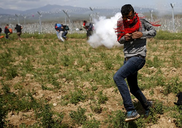 Un migrant fuit des gaz lacrymogènes fument jetés par la police macédonienne sur une foule de plus de 500 réfugiés et migrants qui protestaient contre la fermeture de la frontière gréco-macédonienne près du village de Idomeni, Grèce